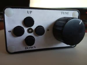 The front panel contains the tuning knob on the right side and four buttons in a cross configuration on the left